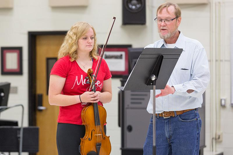 Professor working with a student holding a violin