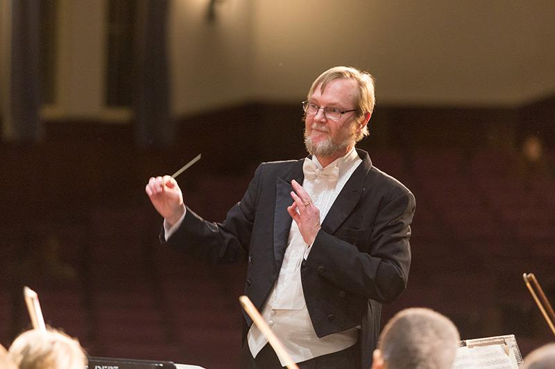 Orchestra conductor leading an group
