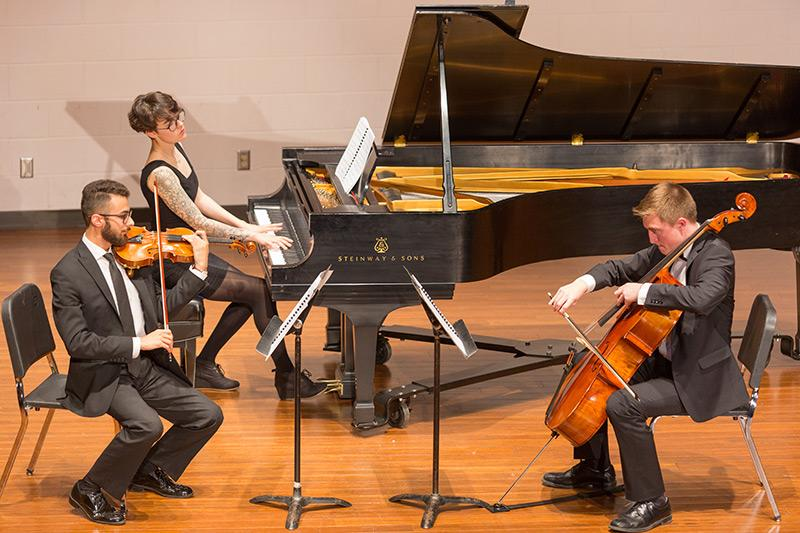 Orchestra students playing string instruments and piano