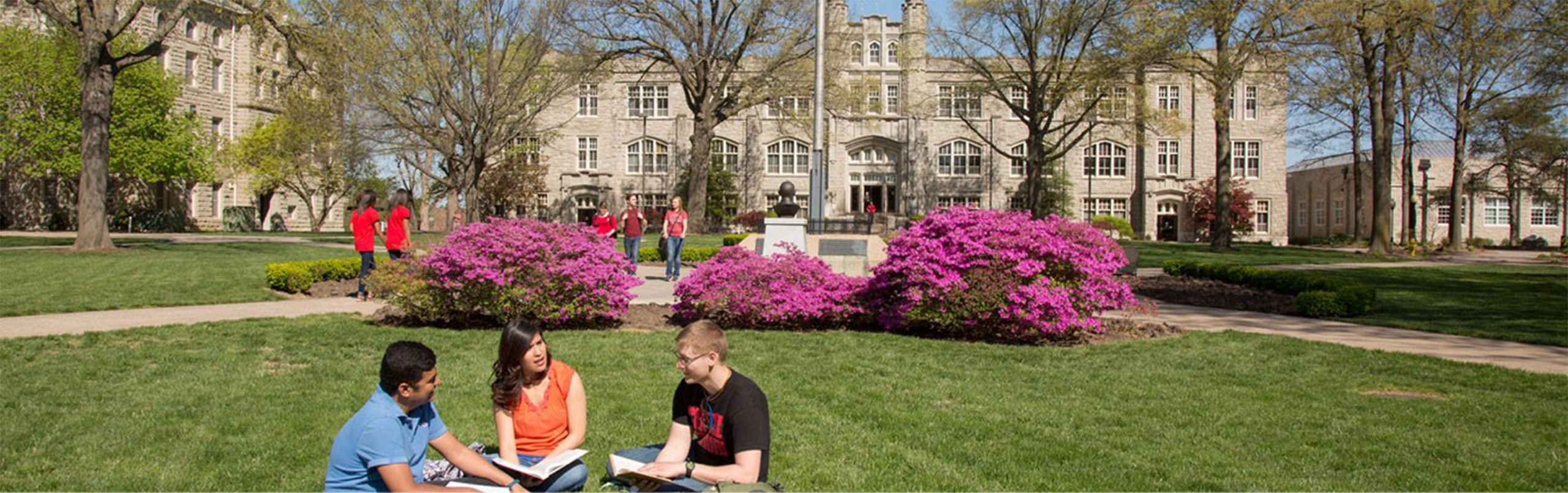 Three students sitting on the grass on campus