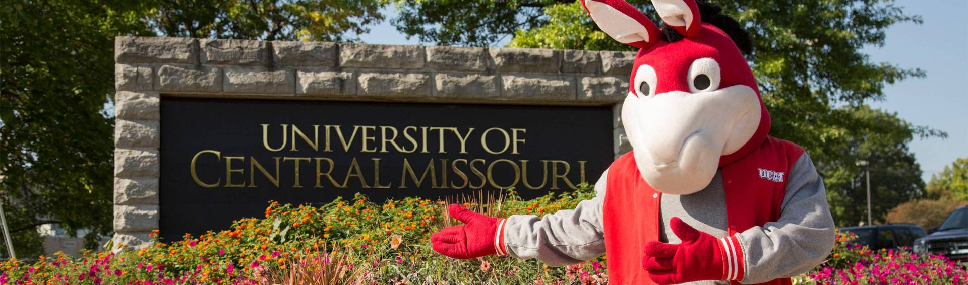 University of Central Missouri welcome sign with Mo the Mule standing beside it