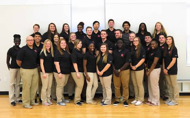 Three rows of athletic training students taking a posed picture in their black UCM polos and kacki pants.
