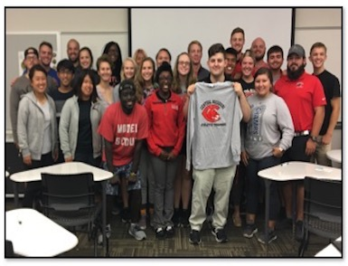 students standing in a classroom for a group photo. One is standing holding up an athletic training t shirt