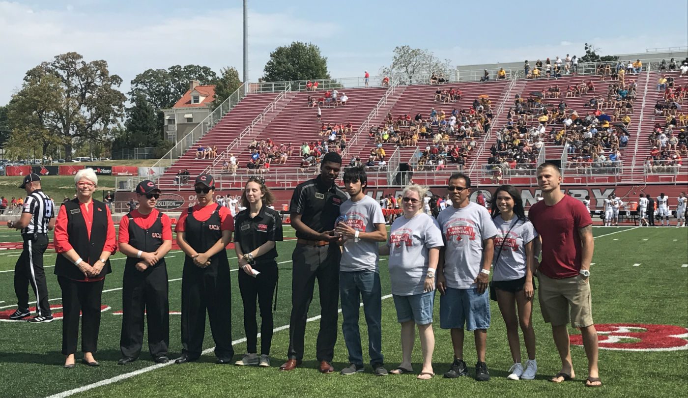 2018 Family of the Year on the football field with the Provost and USHA president.