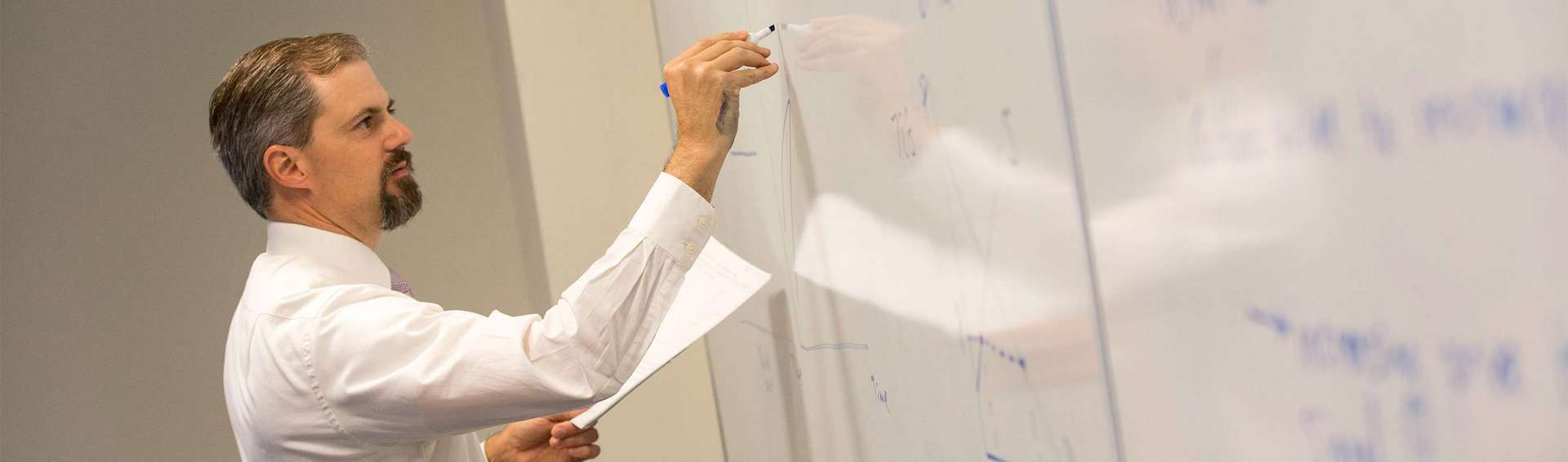 Professor writing on a white board.