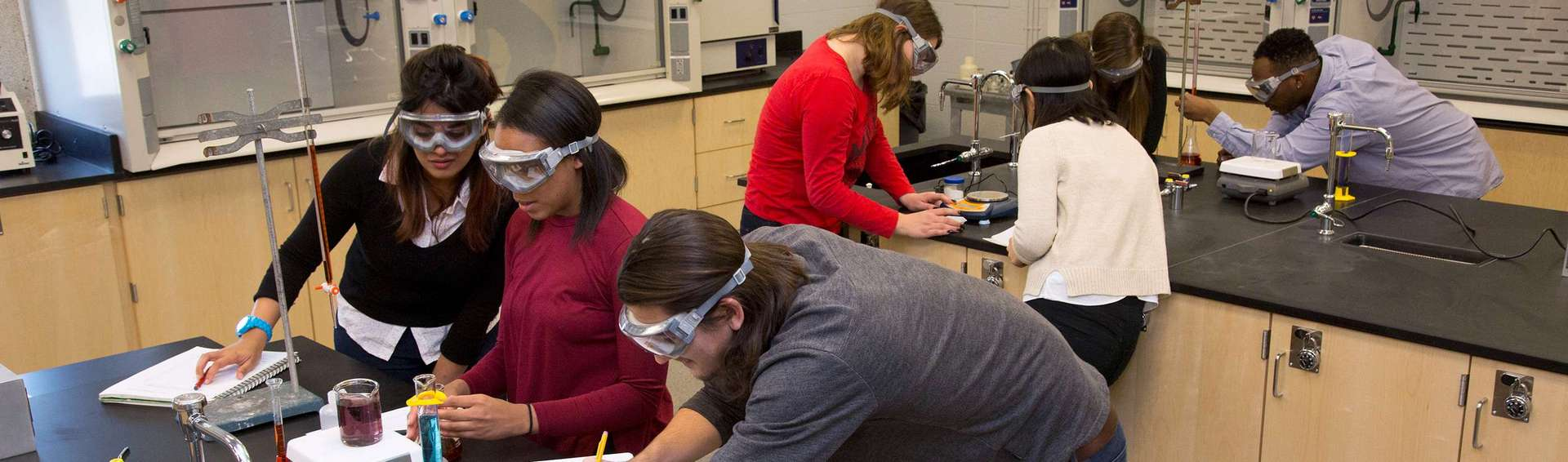 Two groups of students wearing goggles are working at separate benches in a modern undergraduate chemistry lab.