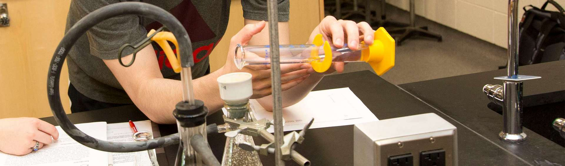 Close up of hands and chemistry equipment.
