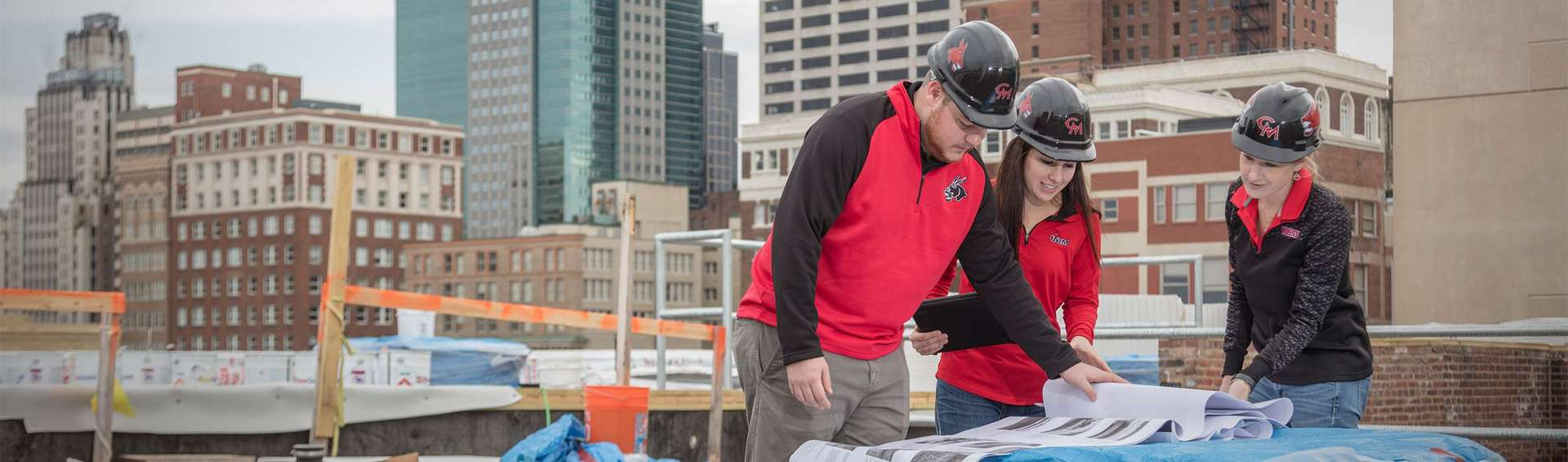 Three students, two female and one male, are standing on the roof of a building in a city, looking at plans. They are wearing UCM shirts and hard hats.
