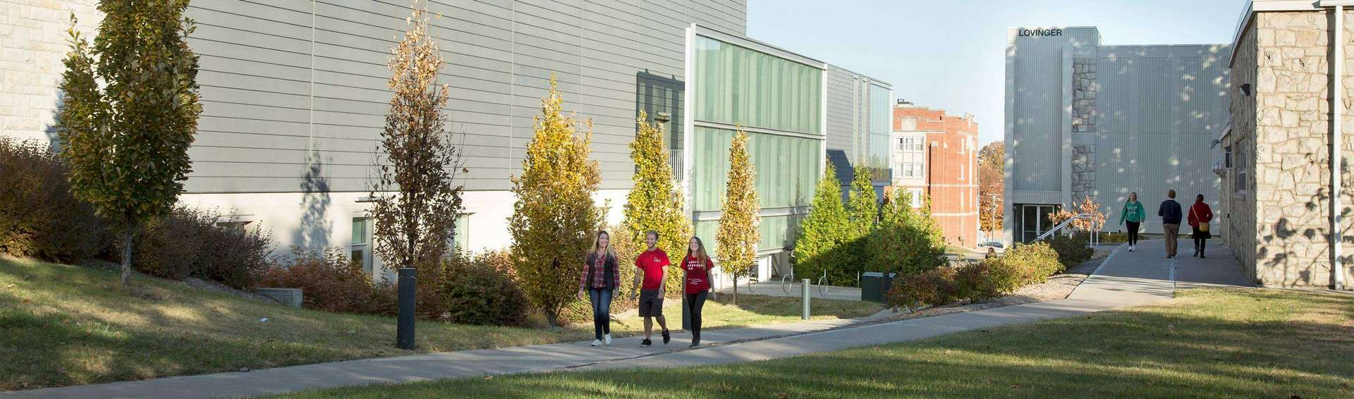 Three student walking at a distance next to the student recreation and wellness center