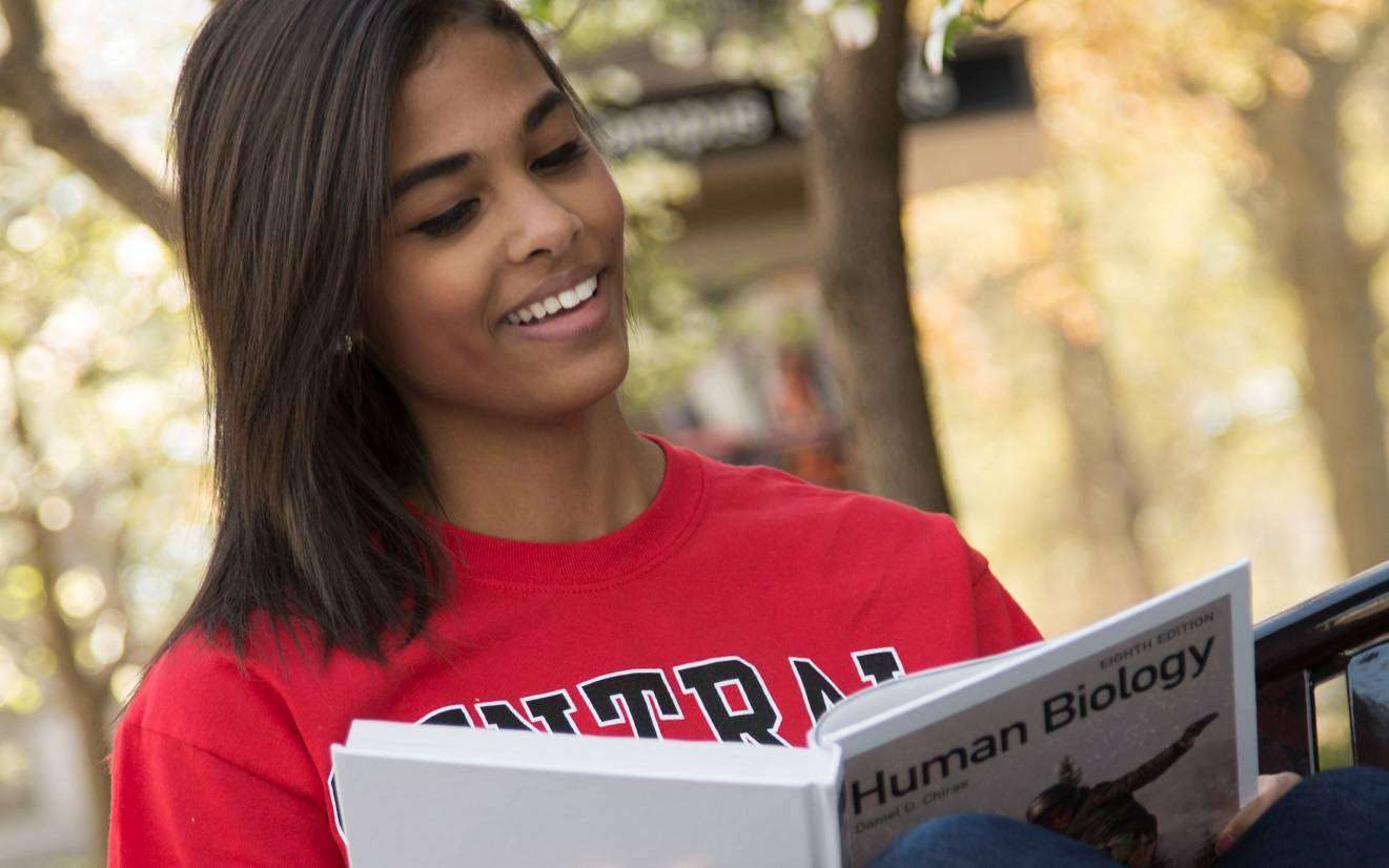 Thumbnail: UCM student reading outdoors
