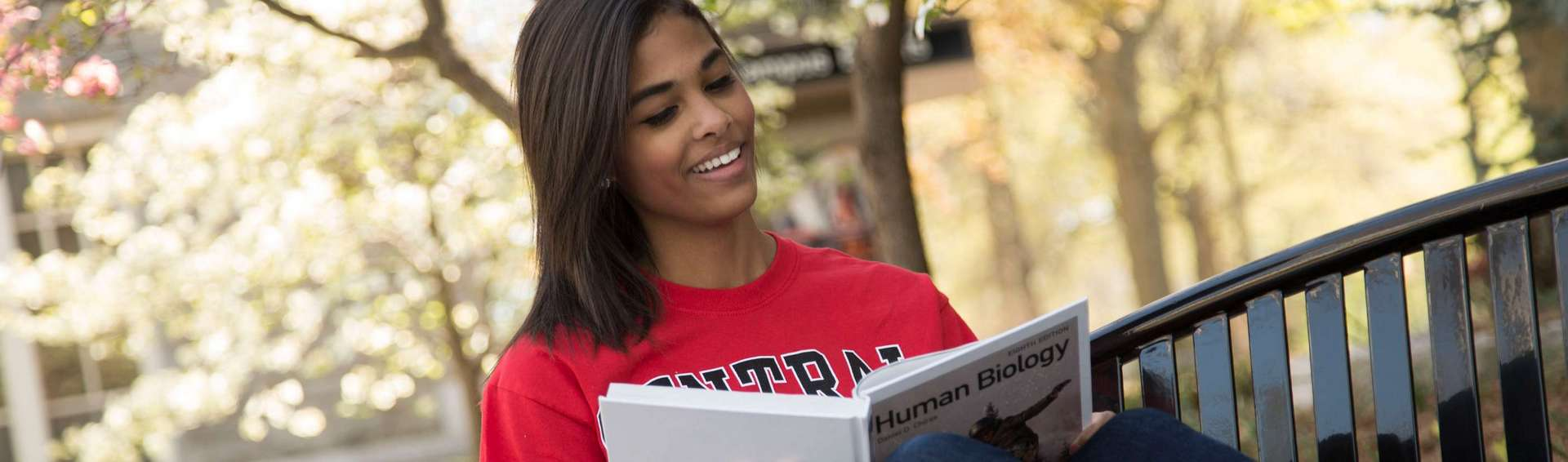 UCM student reading outdoors