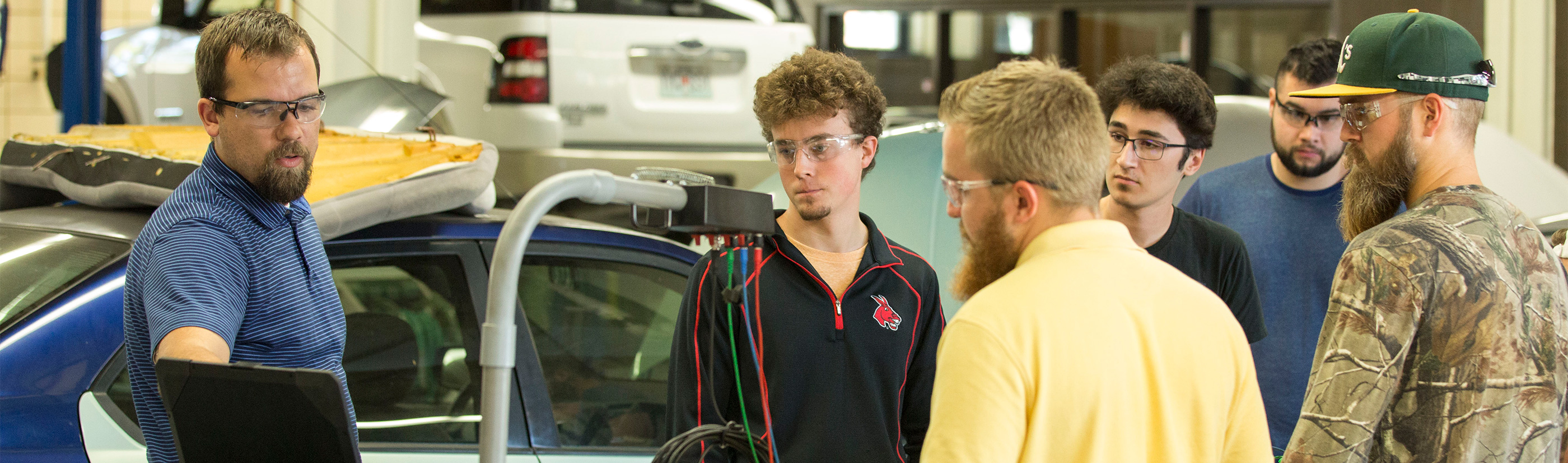 A group of students are watching an instructor use a diagnostic computer in an automotive lab.