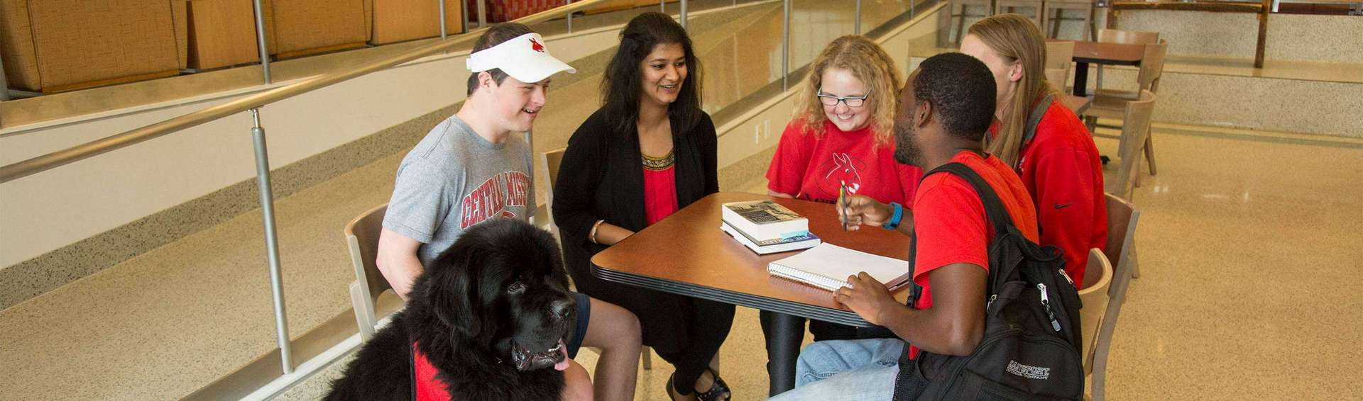 several students sitting at a dining table enjoying a conversation with a black therapy dog sitting next to the table