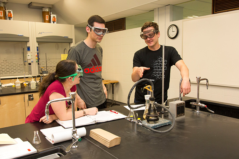 Dr. Steinkruger assisting students with their chemistry research