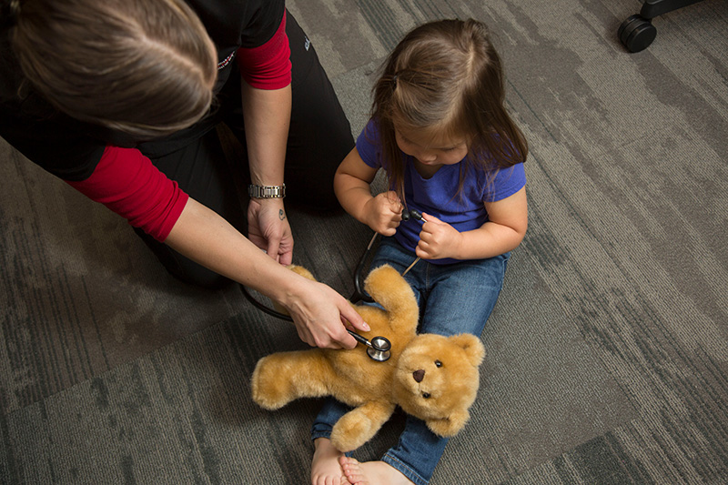 Nursing student with a child and teddy bear