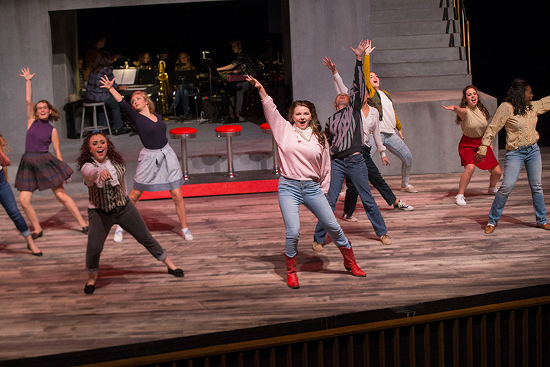 Students dancing and singing in a production of Footloose