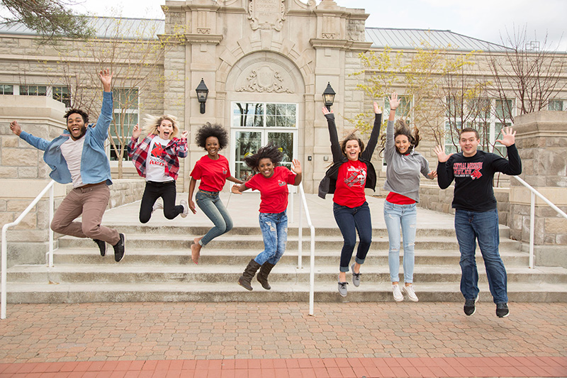 Diverse group of students jumping in air