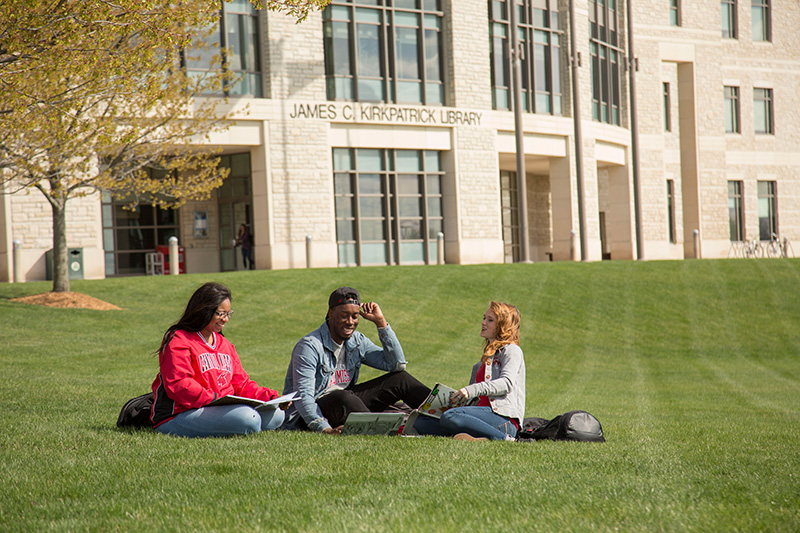 students sitting on the lawn at the library