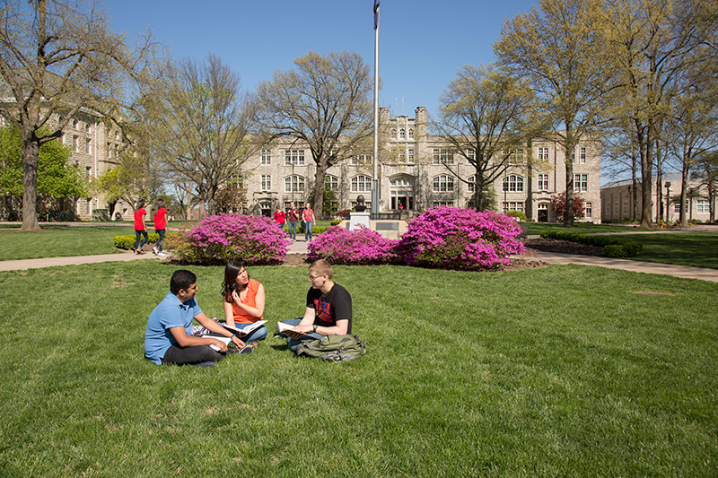 three students sitting on the grass in the quad
