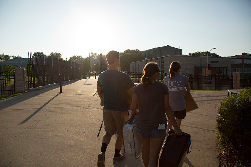 three students walking away from the camera into the sun