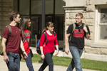 four students walking on campus talking