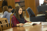 female student studying at desk in library