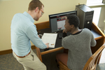 man helping student sitting at computer