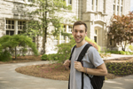 male student wearing backpack on campus